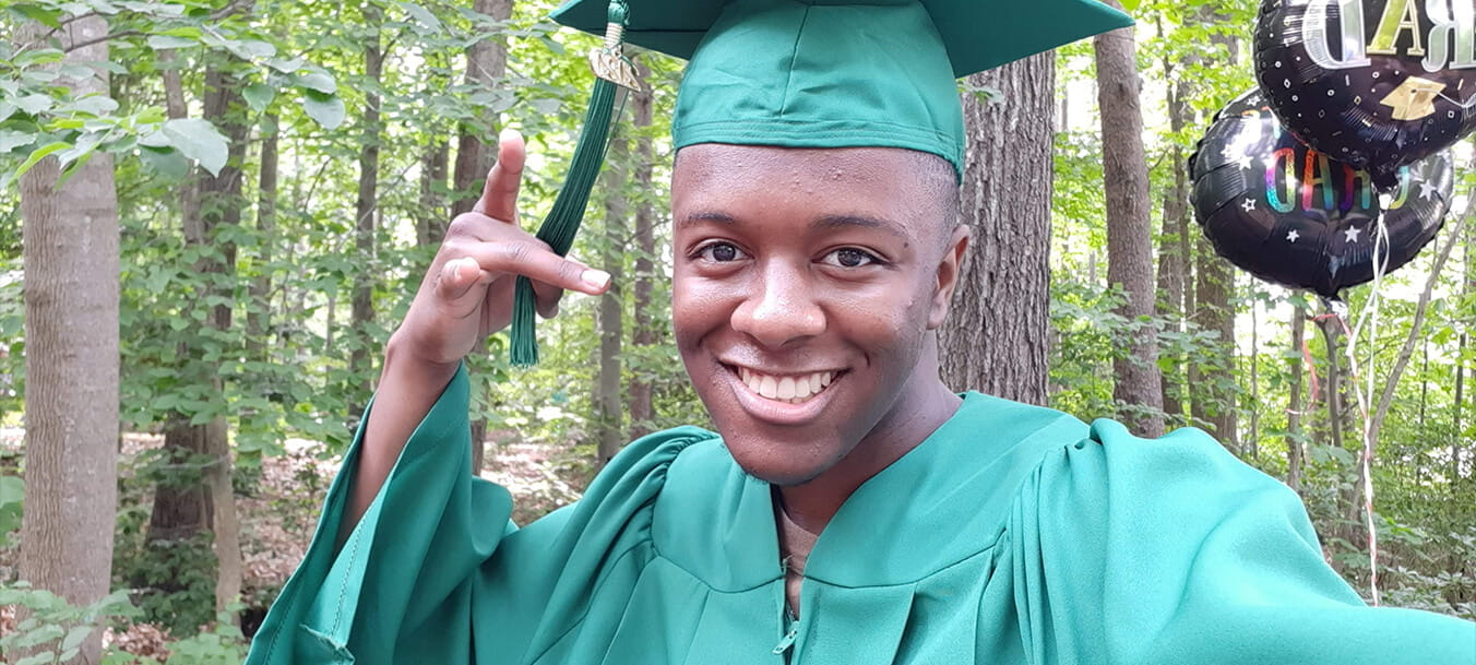 Student Donovyn James poses and smiles into the camera while wearing a green graduation cap and gown.