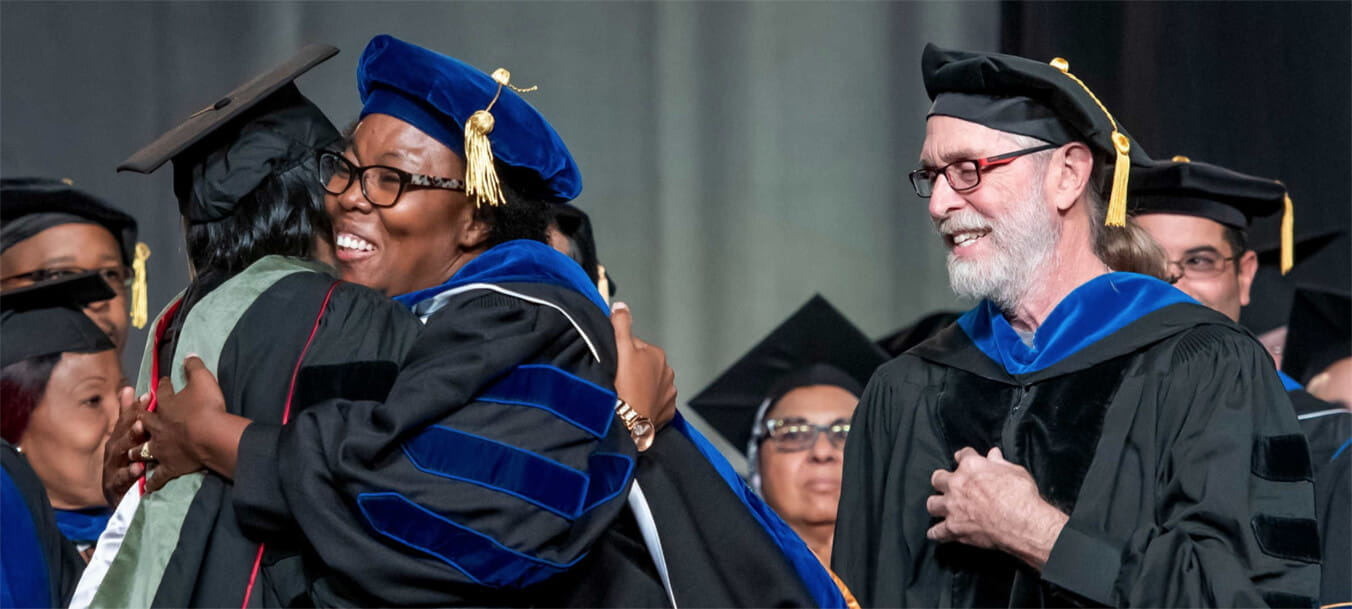A Walden University doctoral graduate hugs a woman in celebration as others look on, smiling.