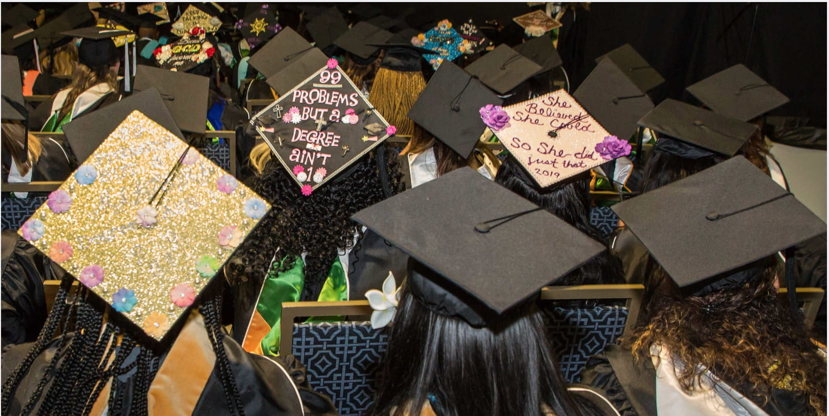 Walden University students with decorated mortarboard caps sit in rows during commencement.