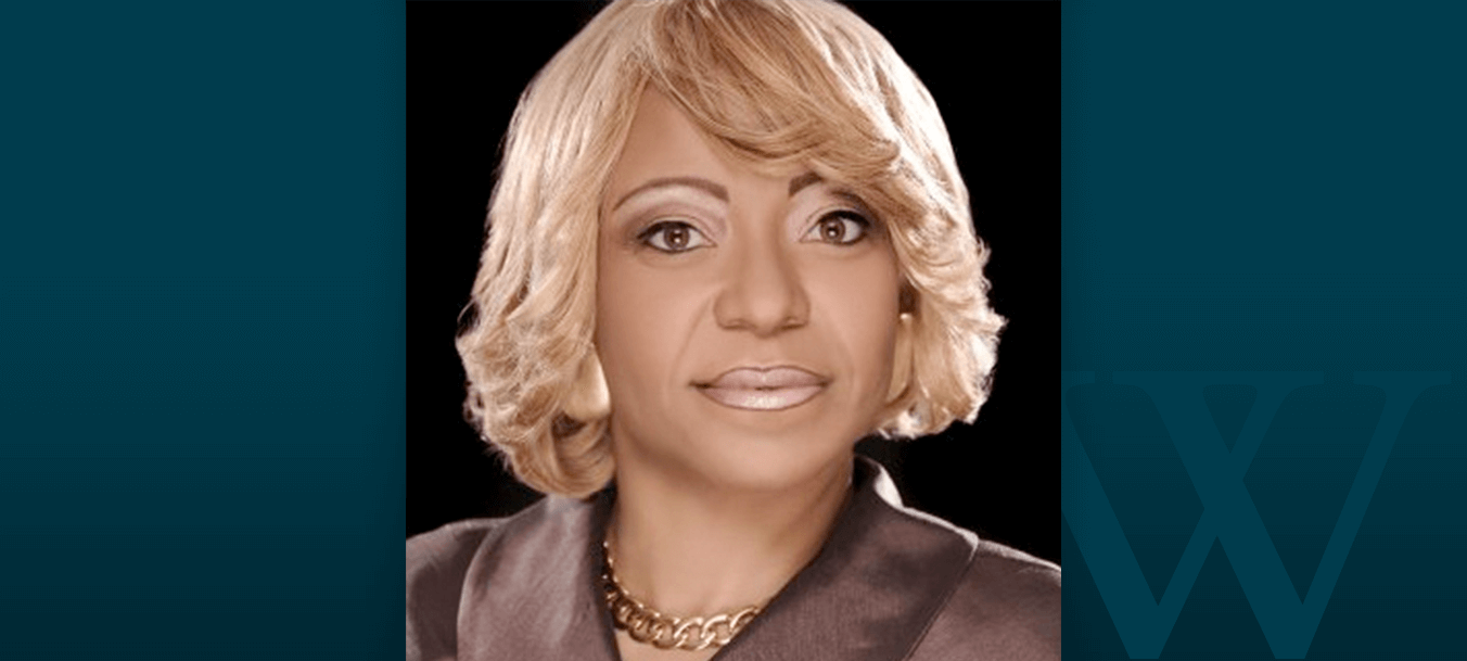 Walden University alumna Val Taylor looks into the camera in front of a black backdrop.