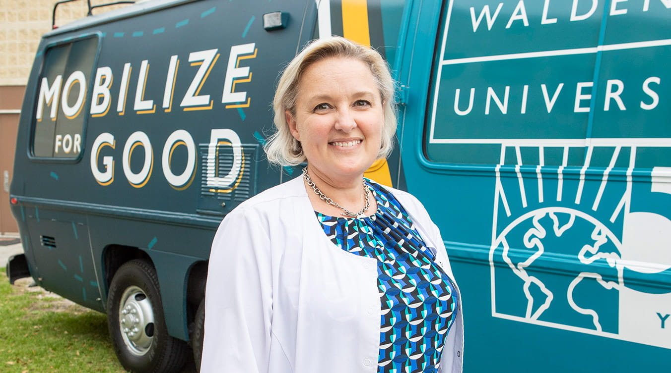 Walden University alumna and nurse Katie Patel stands in a white coat in front of the Mobilize for Good RV.