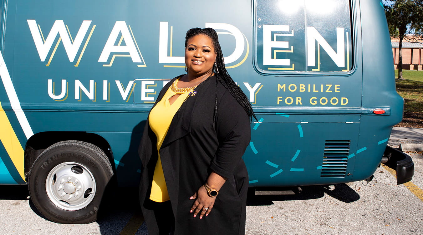 Walden University alumna and educator Tanya Batchelor Judge stands in front of the Mobilize for Good RV.