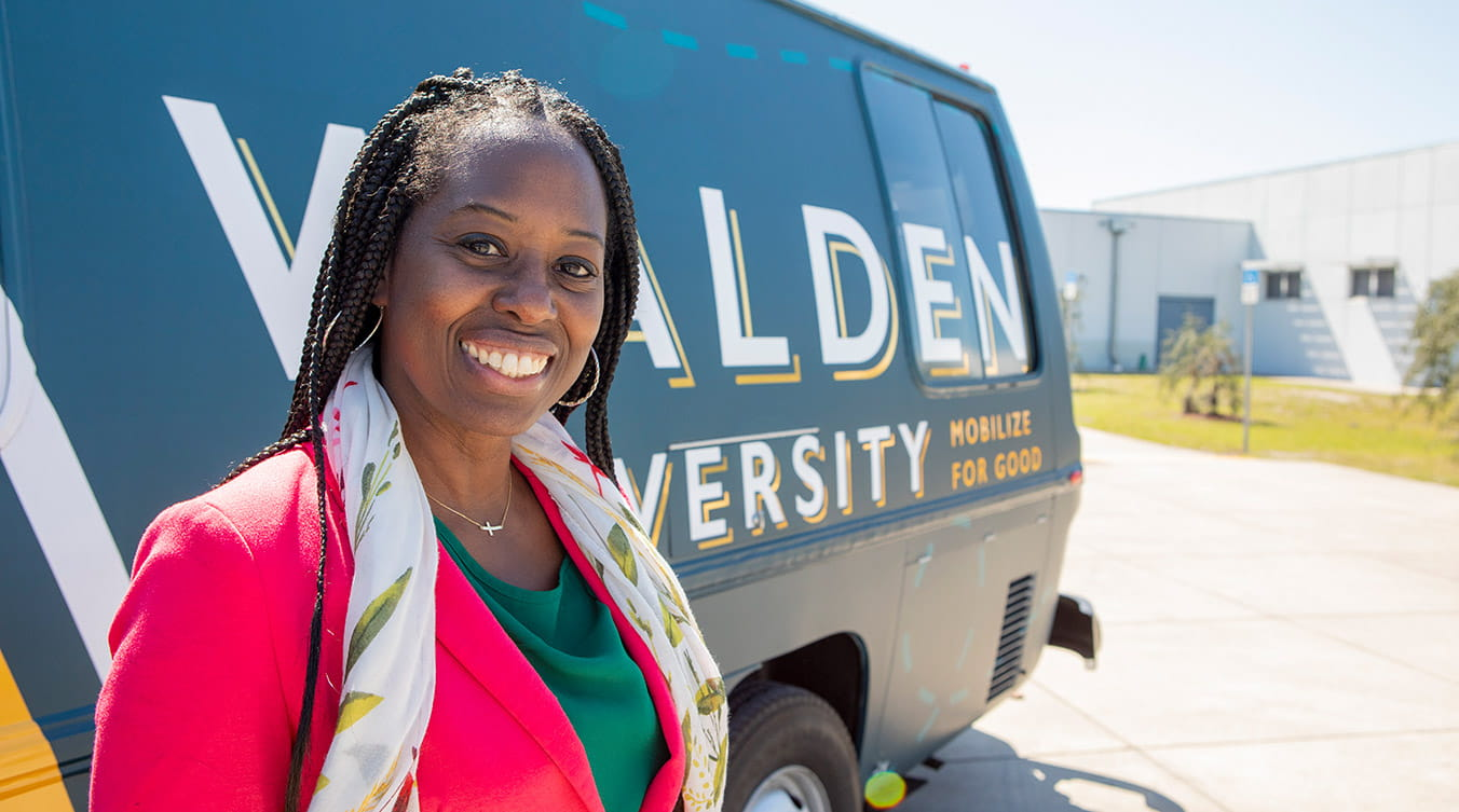 Walden University alumna and teacher Tennith Scott stands in front of the Mobilize for Good RV
