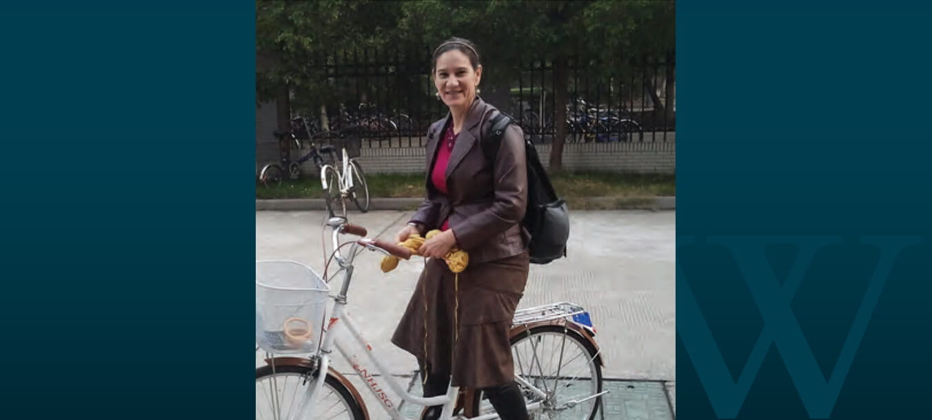 Dressed in a long leather coat, Dr. Annette Padilla pauses on a bike.
