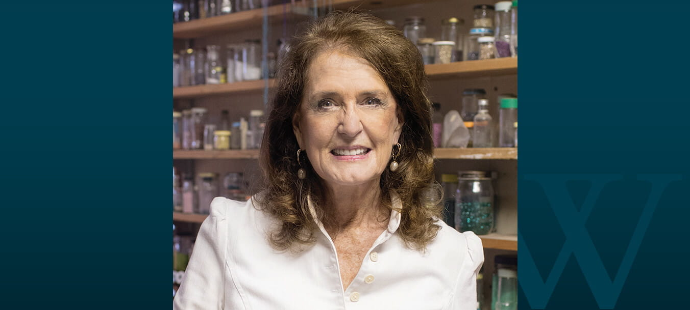 Dr. Carol Ikard poses in front of shelves lined with multi-sized jars.