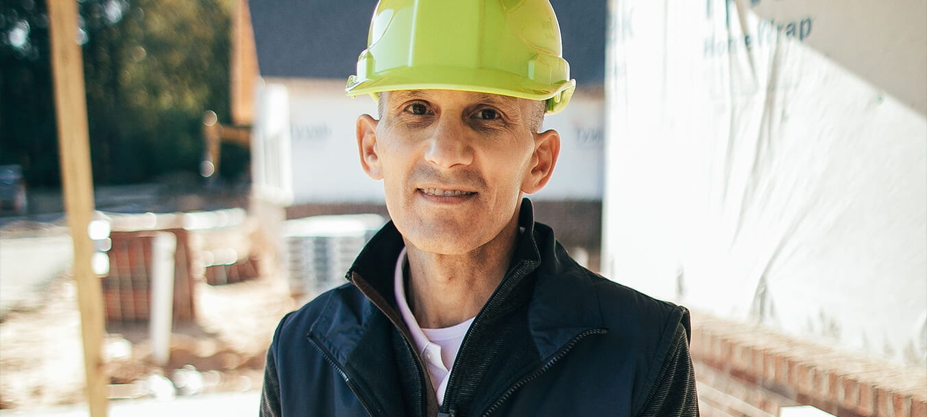 Thomas Gorry stands in a yellow hard hat in front of a construction site.