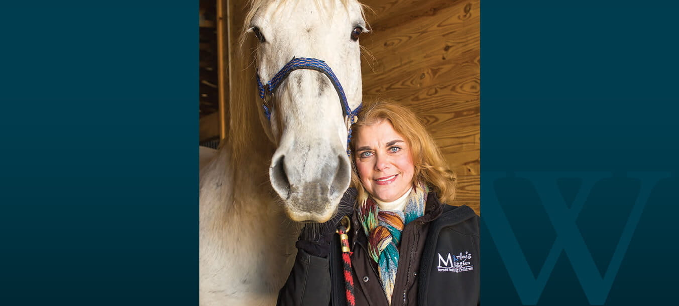 Kimberly Portanova-Feibus leans her cheek against the head of a white horse in a stable.