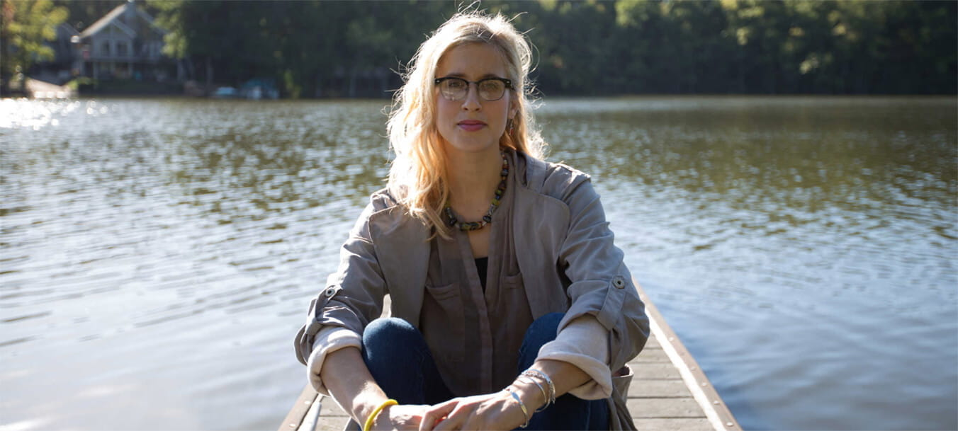 Nutritionist Aubrey Mast sits facing the camera on a dock that extends into a North Carolina lake.