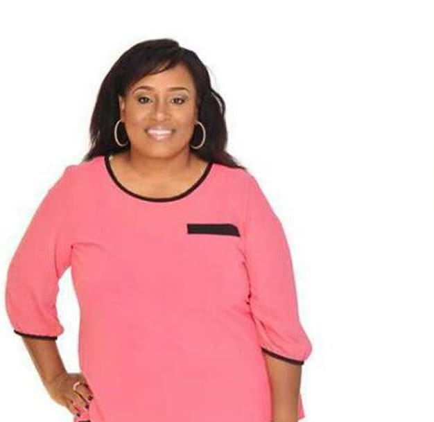 Dionysica Stewart poses with her hand on her hip in front of a white background.