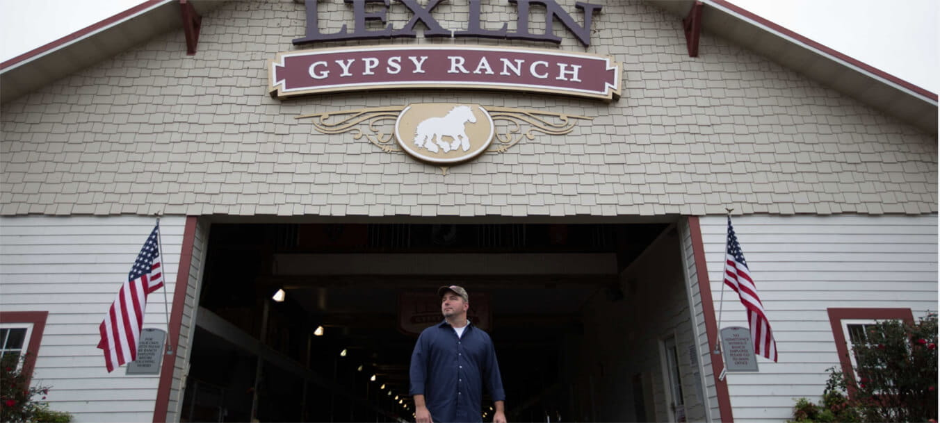Dr. Eric W. Barton stands in front of the open barn doors of LexLin Gypsy Ranch, two U.S. flags waving beside him.