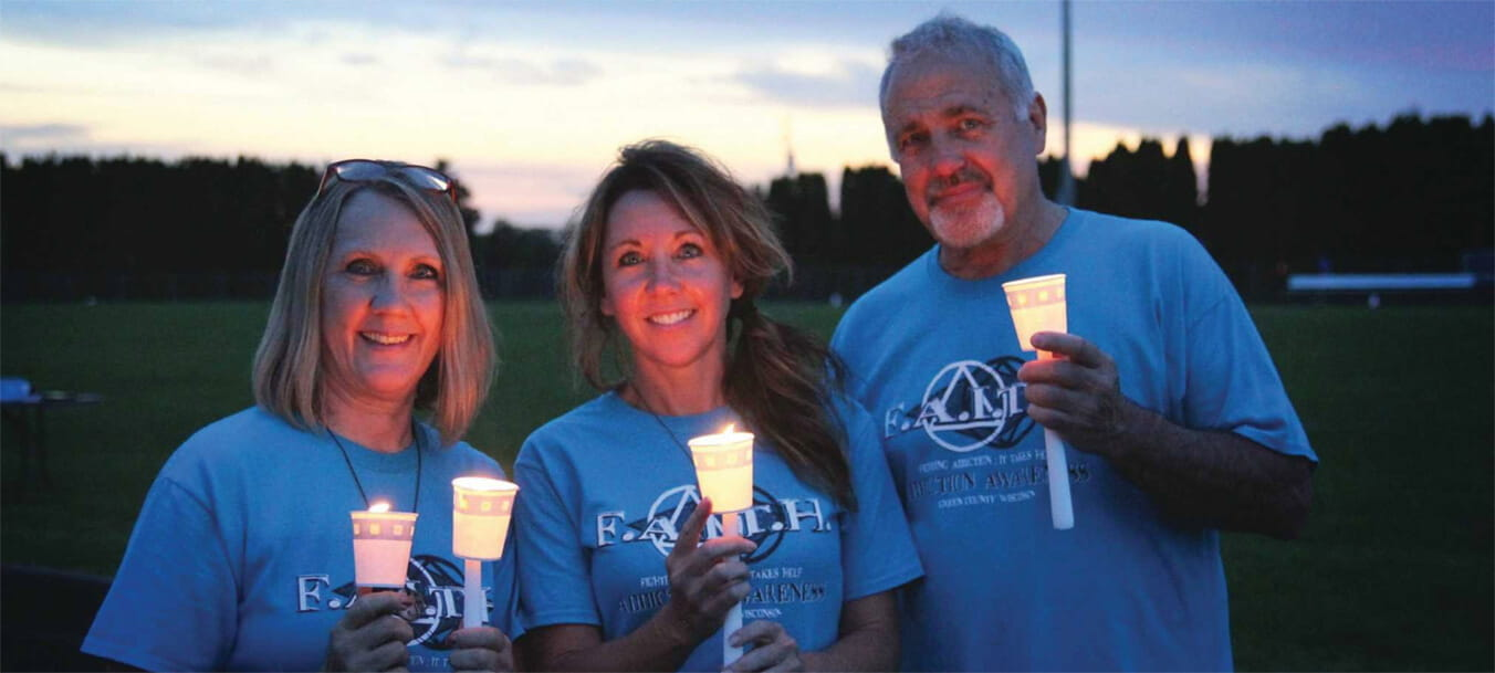 Jackie Moon stands between a male and female FAITH volunteer on a field at dusk, all three of them holding lit candles.
