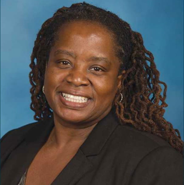 Dr. Nina Nabors smiles for a photo in front of a blue background.