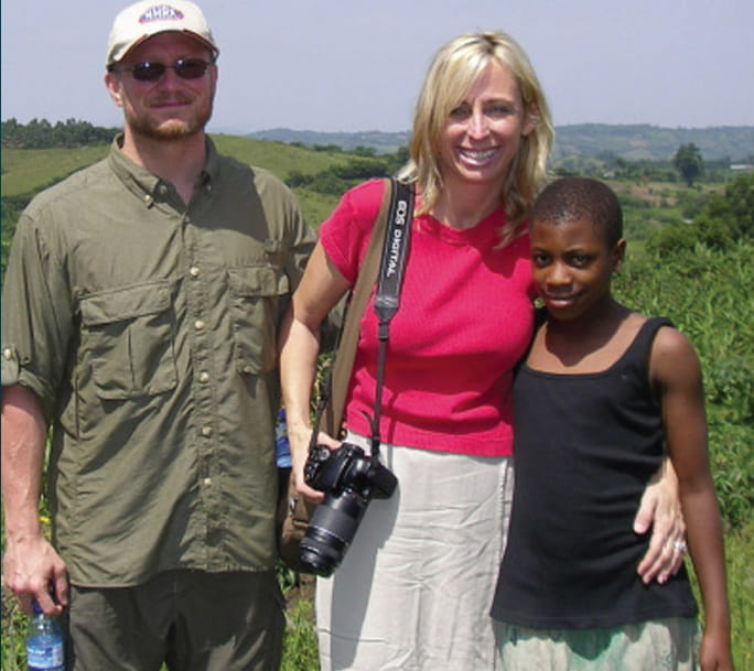 Dr. Shannon Irvine stands with a Ugandan child and male assistant in front of the green fields of Uganda.