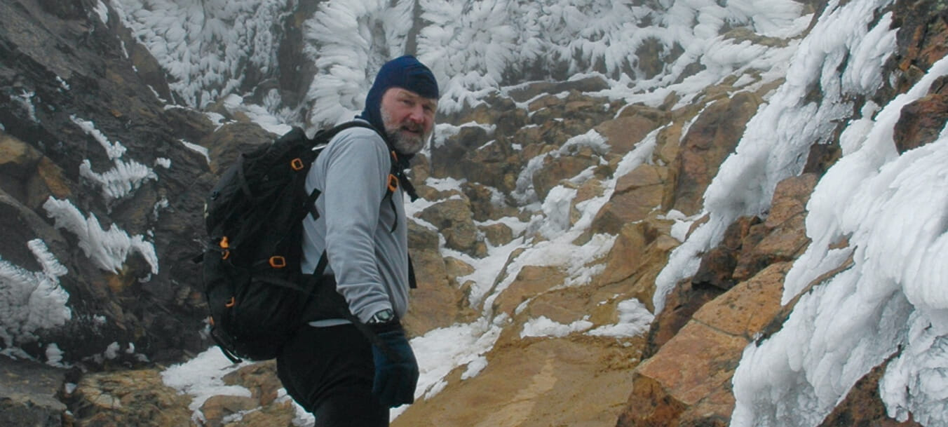 Dr. Steve Gardiner looks back over his shoulder while paused on a steep and icy path that ascends a craggy mountain.