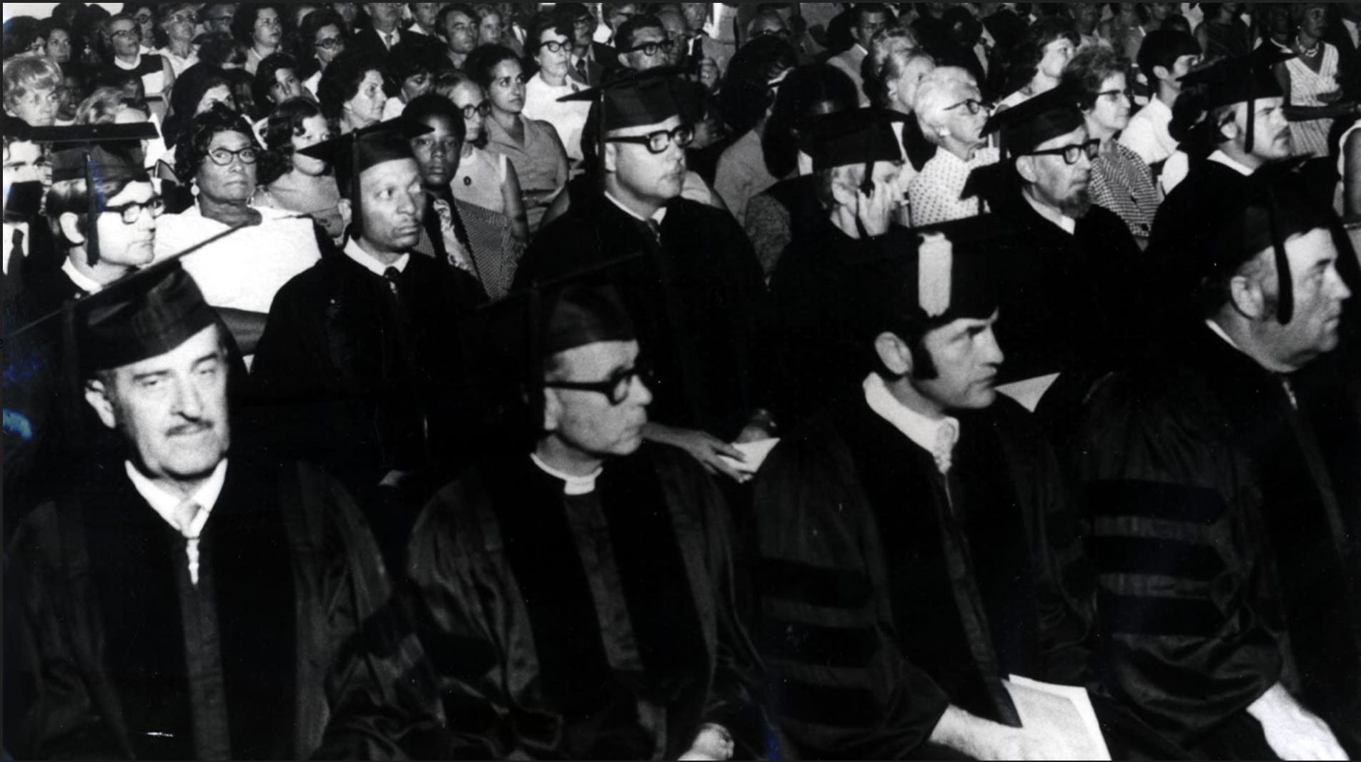 Black-and-white image of Walden University's first class of graduates sitting during the commencement ceremony.